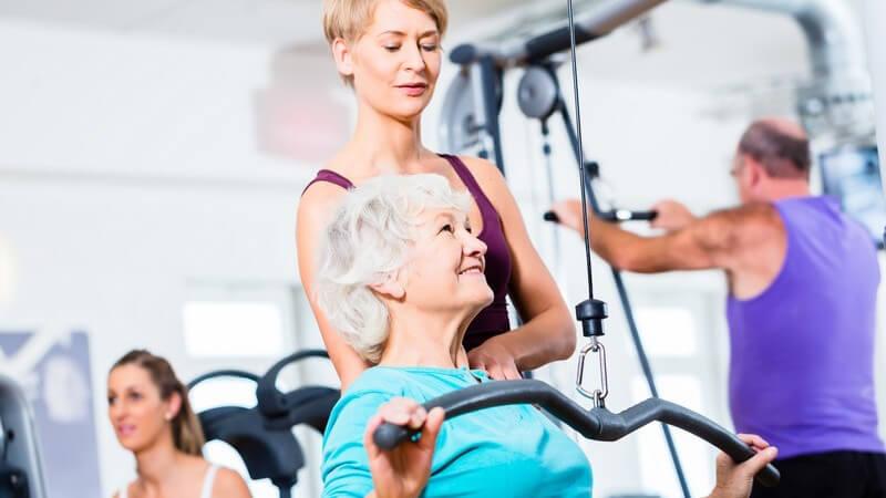 Seniorin beim Rückentraining mit Personal Trainerin im Fitness-Studio