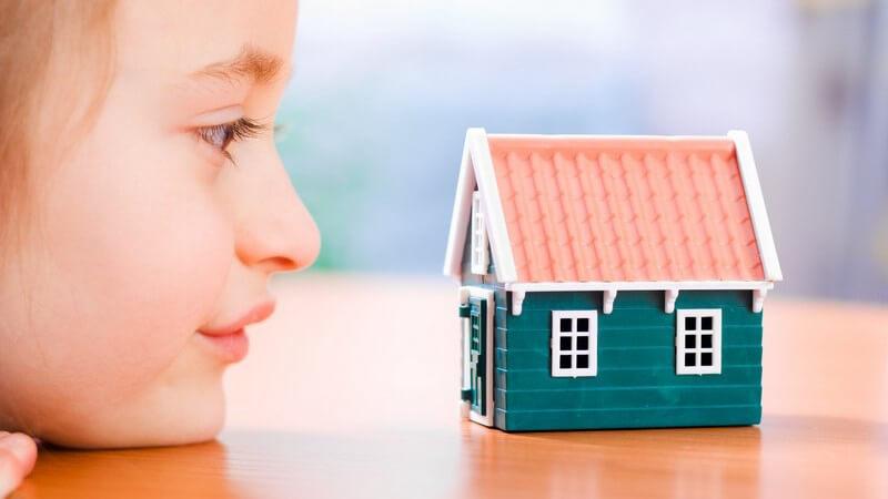 Kleines Mädchen mit Kinn auf Tischplatte schaut sich kleines Modellhaus an