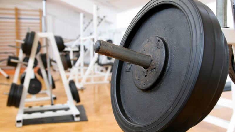 Nahaufnahme von schwarzen Hantelscheiben in einem Fitness-Studio mit weißen Geräten