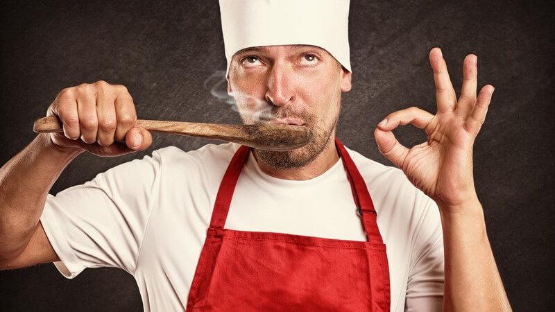 Koch mit Kochmütze und roter Schürze schmeckt dampfende Soße mit einem Holzlöffel ab