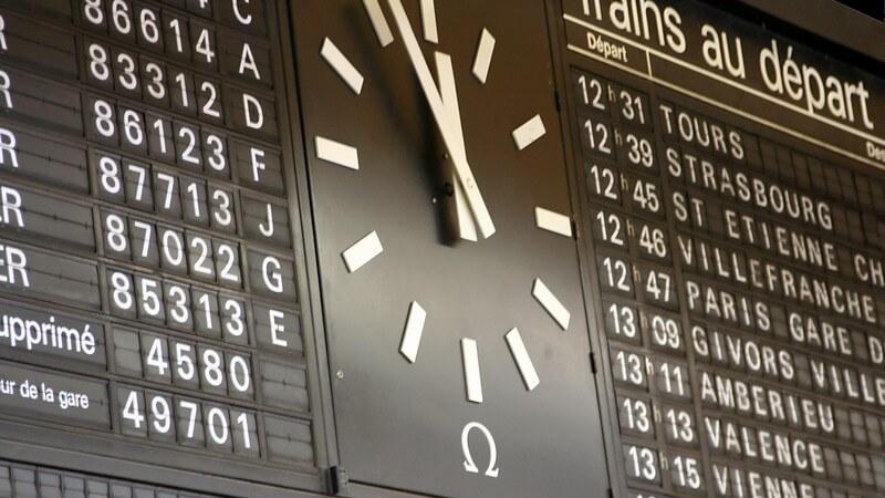 Abfahrtstafel mit Uhr am französischen Bahnhof, Uhrzeit kurz vor Zwölf