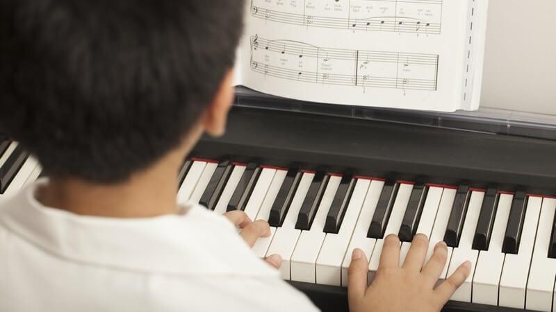 Asiatischer Junge spielt Klavier nach Noten