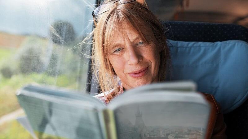 Frau sitzt im Zug am Fenster und liest im Reiseführer