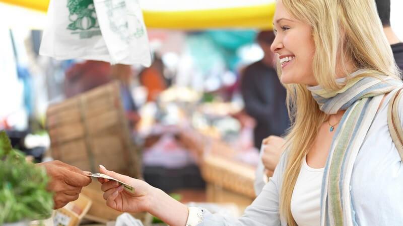 Blonde frau mit grauem Schal kauft in einem Lebensmittelmarkt