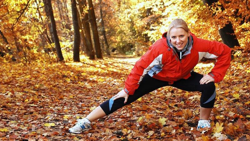 Junge blonde Joggerin macht Dehnübungen im Wald, Herbsttag