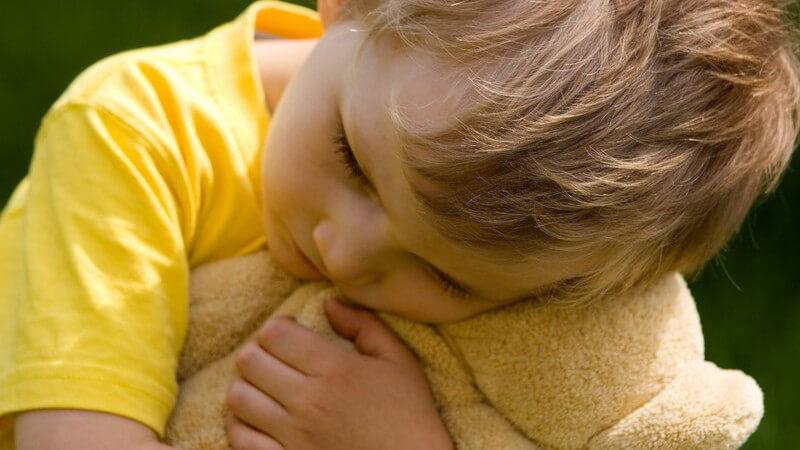 Kleiner Junge in gelbem T-Shirt knuddelt mit seinem beigefarbenen Teddy