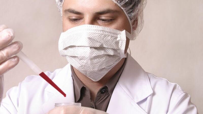 Untersuchung - Chemiker mit Mundschutz bei einer Blutuntersuchung