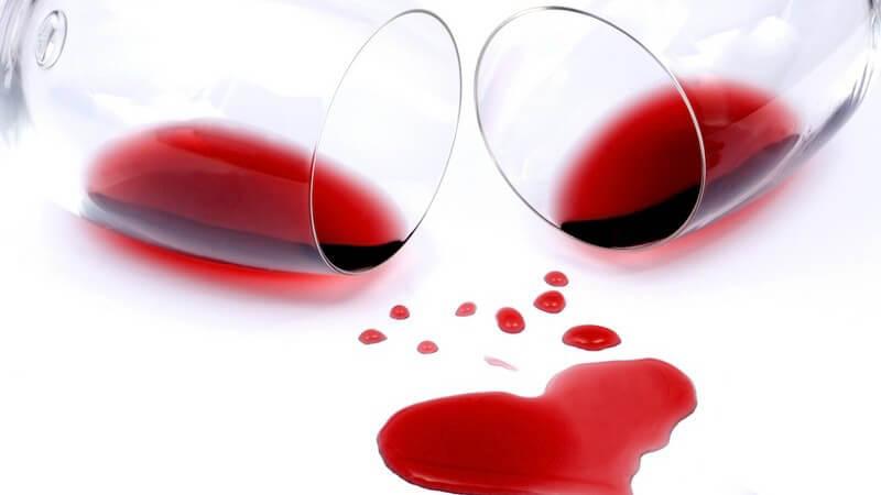 Zwei Gläser mit Rotwein gekippt, darunter Rotweinfleck in Herzform