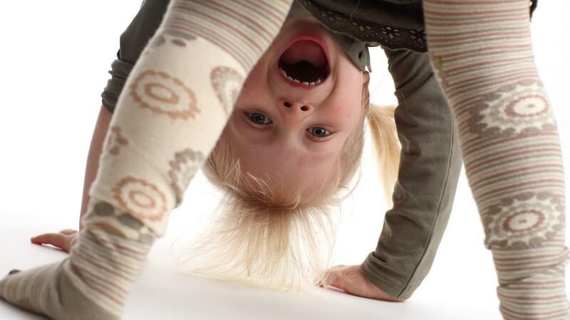 Kleines Mädchen auf Händen und Füßen gestützt, schaut durch Beine in Kamera