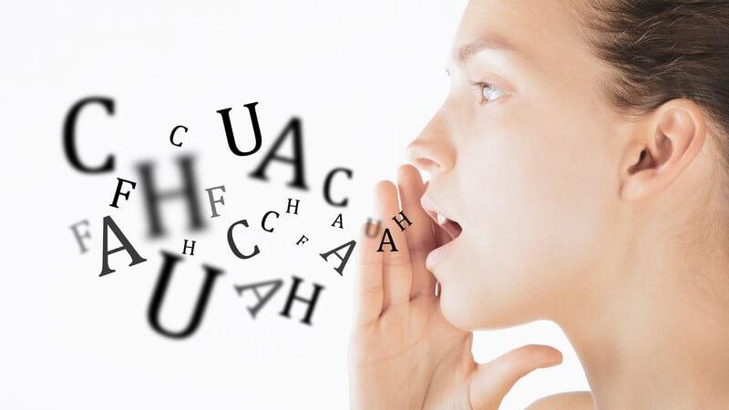 Seitliches Portrait einer Frau mit der rechten Hand an ihrem geöffneten Mund, aus dem Buchstaben kommen (Fotomontage)