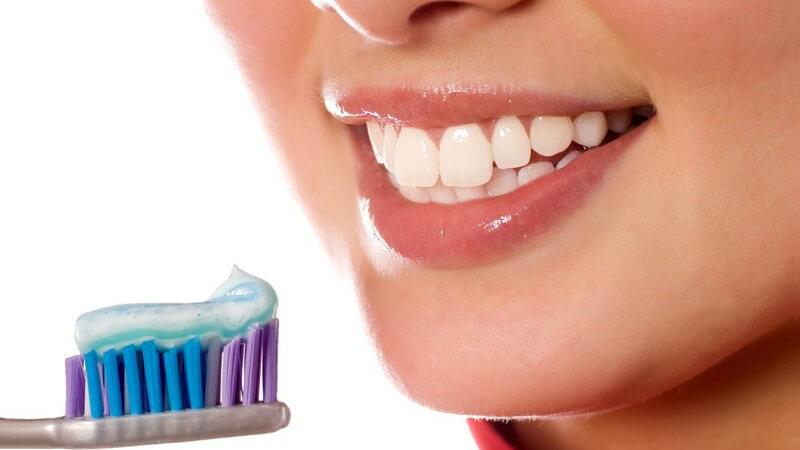 Lächelnder Frauenmund, Zahnbürste mit Zahnpasta davor