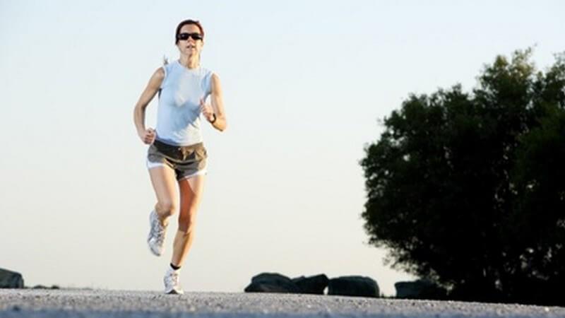 Sportliche Frau mit Sonnenbrille, die Straße hoch joggend