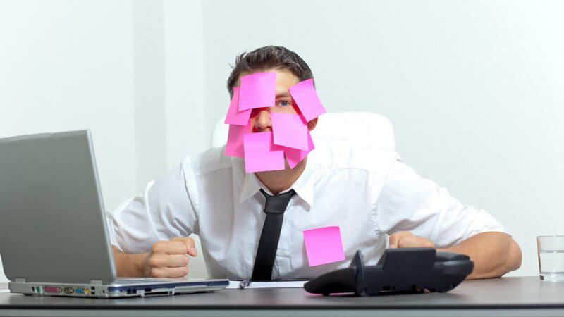 Überforderter Geschäftsmann hat Post-it Zettel im Gesicht kleben