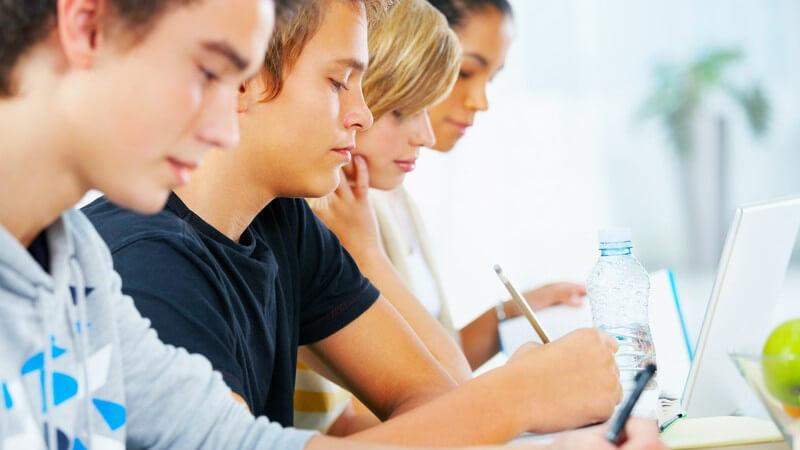 Reihe von Jugendlichen am Tisch konzentriert bei der Arbeit