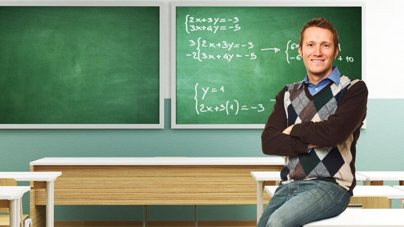 Junger Lehrer sitzt auf Tisch in Klassenzimmer, im Hintergrund Tafel mit Matheformeln