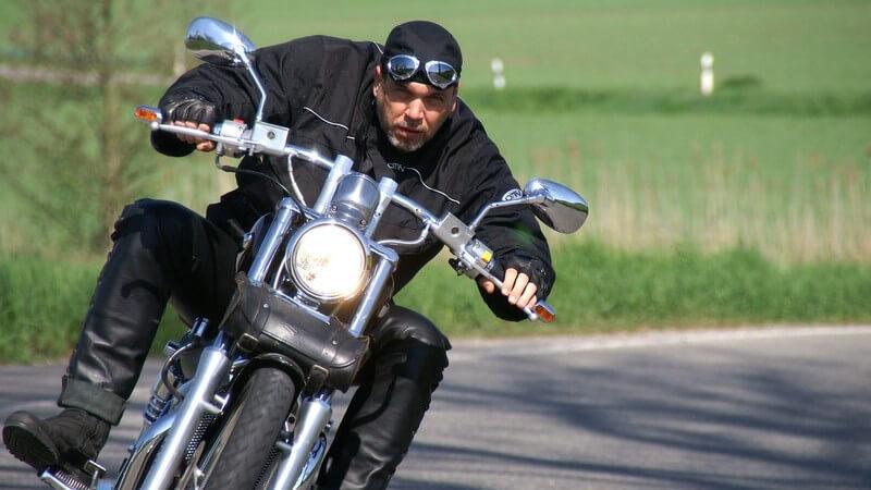 Motorradfahrer in schwarzer Kleidung, Kopftuch kommt um Kurve gefahren auf Kamera zu