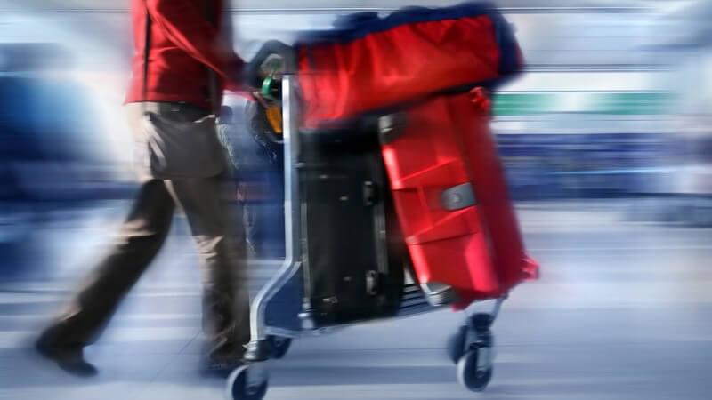 Mann schiebt Gepäckwagen mit roten Koffern