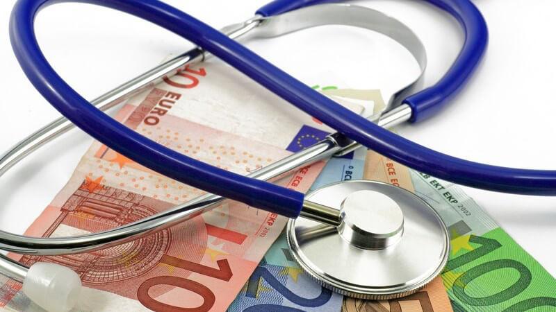 Blaues Stethoskop liegt auf Euro-Geldscheinen