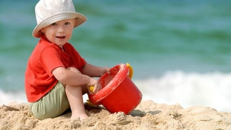Kleiner Junge mit Hut spielt mit Eimer und Schaufel am Strand