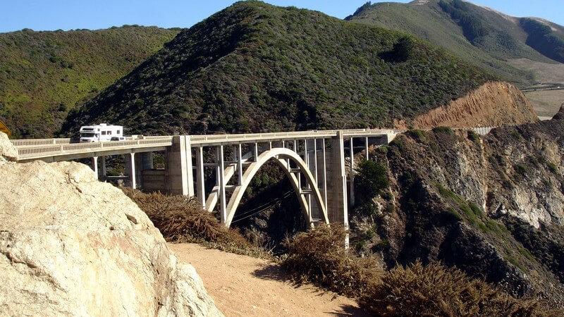 Weiße Bogenbrücke vor grün bewaldeten Bergen, auf der ein weißer Wohnwagen fährt