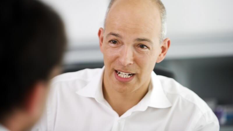 Arzt mit Halbglatze und weißem Poloshirt sitzt mit Patient in der Sprechstunde