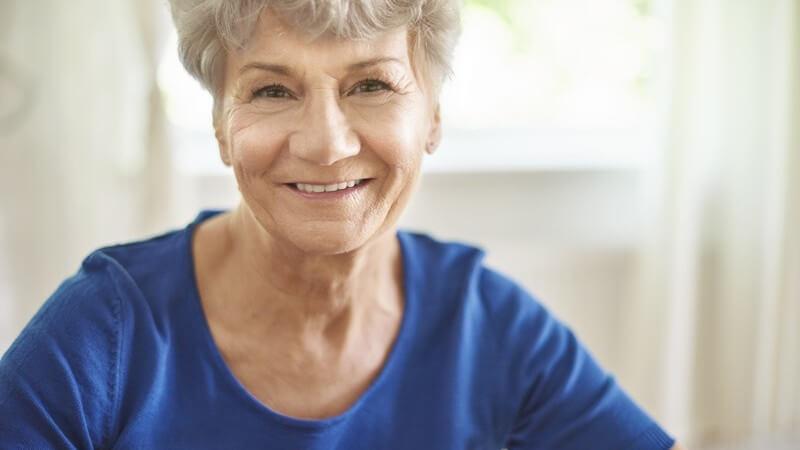 Portrait einer Seniorin mit grauen Haaren und blauem Oberteil, lächelt in die Kamera