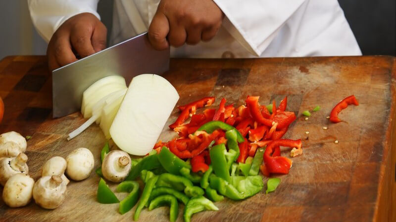 Chefkoch schneidet frisches Gemüse mit großem Messer