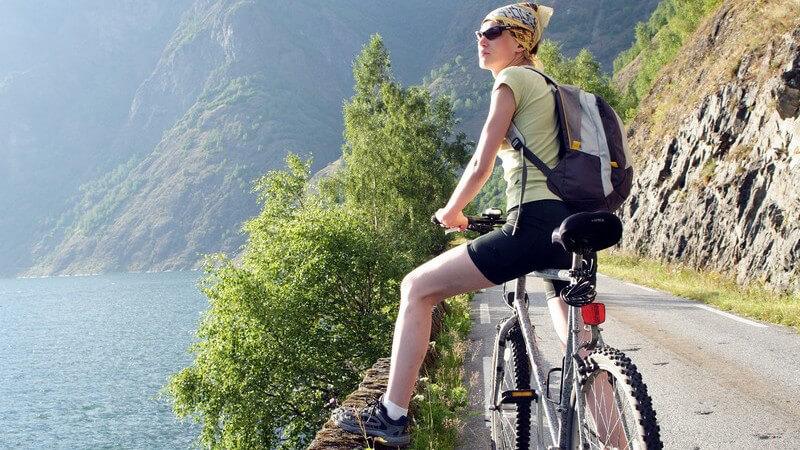 Frau auf Fahrrad oder Mountainbike an Bergstraße mit Sonnenbrille und Kopftuch, die Pause macht und auf Bergsee schaut