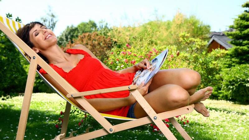 Frau liegt mit Zeitschrift auf Liegestuhl im Garten