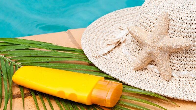 Sonnenhut, -creme und Palmenblatt an Pool