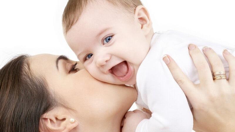 Mutter hält Baby hoch und küsst es auf die Wange, Baby lacht mit offenem Mund