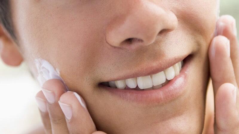 Jugendlicher trägt Rasierschaum auf und lächelt