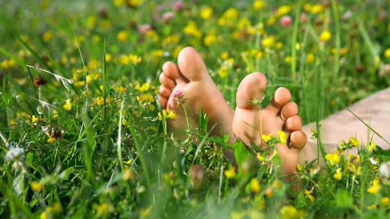 Nahaufnahme nackte Füße in Blumenwiese