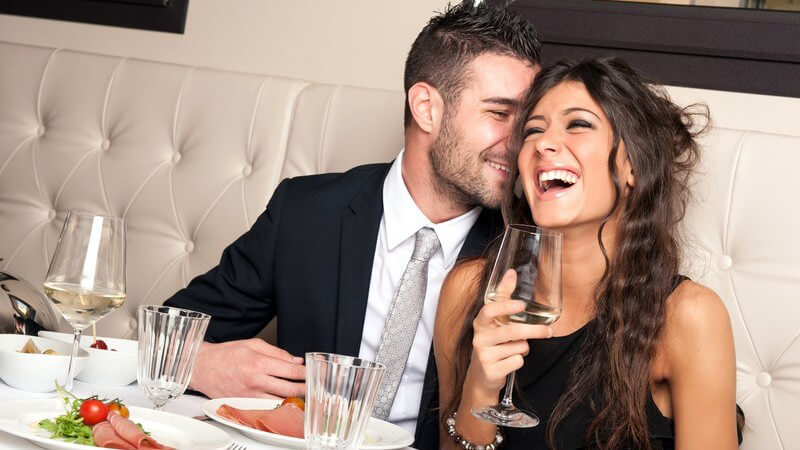 Lächelndes elegant gekleidetes junges Paar im edlen Resturant beim Abendessen