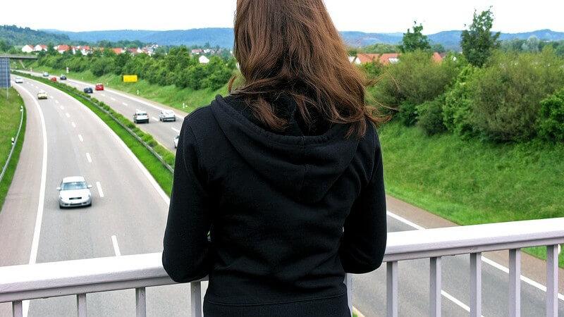 Brünettes Mädchen mit schwarzem Pulli blickt von einer Autobahnbrücke, Kamera von hinten