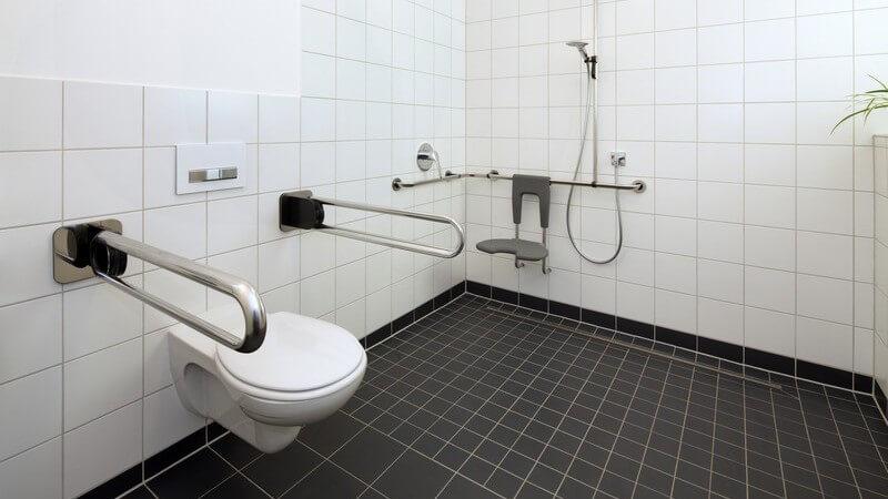 Behindertengerechtes (barrierefreies) Badezimmer mit schwarzen Bodenfliesen und weißen Wandfliesen