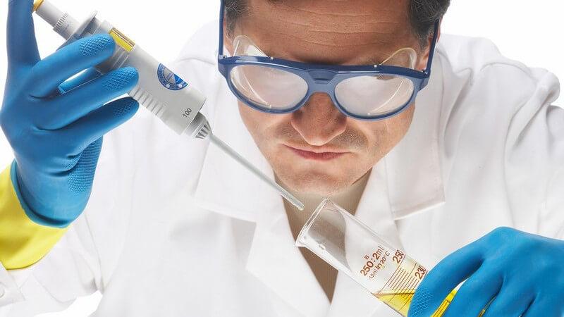 Laborarzt mit Schutzbrille füllt Probe in Reagenzglas