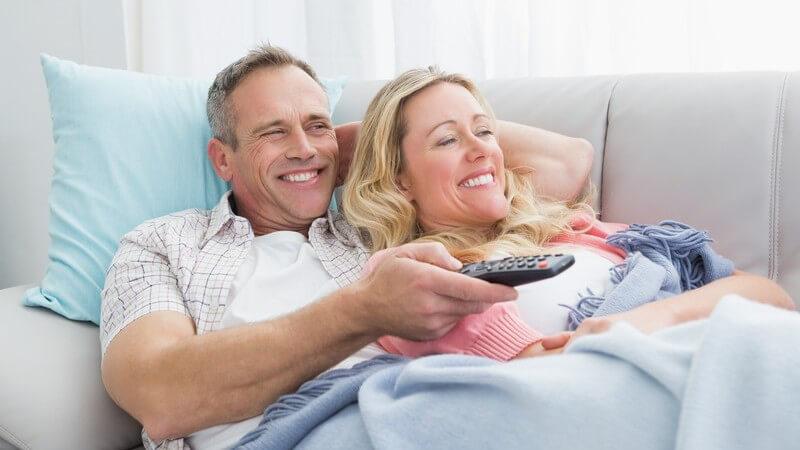 Älteres Paar liegt eingekuschelt auf der Couch und guckt Fernsehen