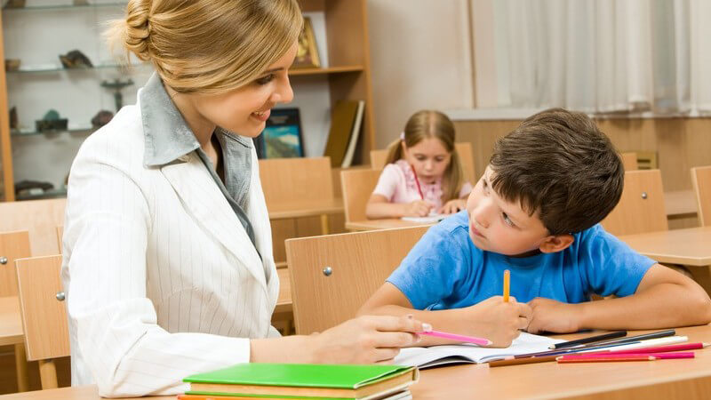 Junge Lehrerin sitzt neben Schüler in Klasse an Tisch, hilft bei Hausaufgaben, Klassenhefte neben ihr, Schülerin hinten