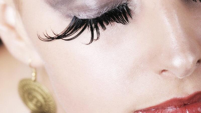 Stark geschminktes Frauengesicht mit geschlossenen Augen und extrem langen Wimpern