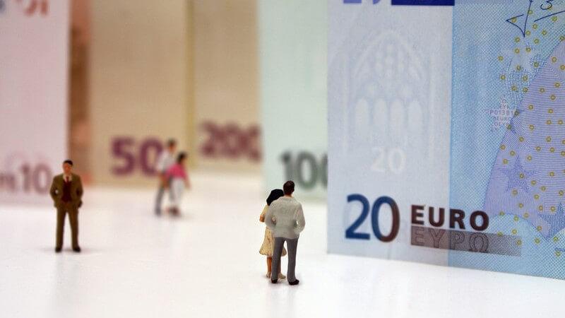 Winzige Personen stehen vor riesigen Euroscheinen