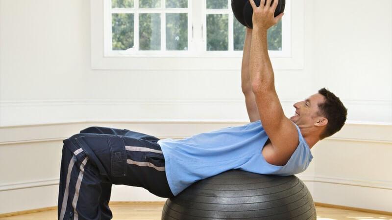 Mann in blauer Fitnesskleidung liegt auf dem Rücken auf schwarzem Gymnastikball und hebt schwarzen kleien Ball nach oben