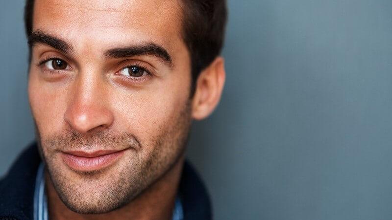 Attraktiver junger Mann mit Dreitagebart lächelt in Kamera