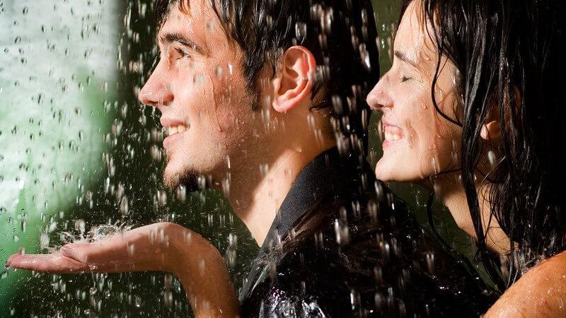Junges glückliches Paar im Regen, sie umarmt ihn von hinten
