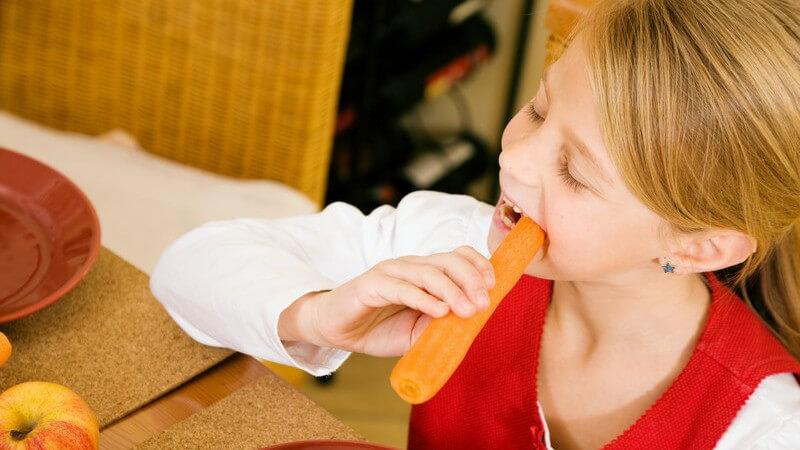 Kleines Mädchen sitzt am Tisch und beisst in Karotte