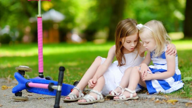 Zwei kleine Mädchen sitzen neben ihren Rollern am Wegesrand, eine ist gestürzt und wird getröstet