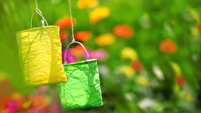 Gelbe und grüne Gartenlaterne, im Hintergrund Blumen und Pflanzen
