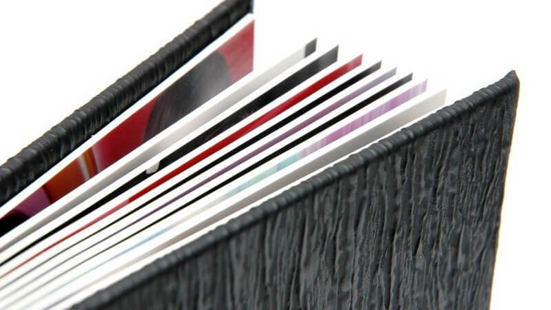 Nahaufnahme eines Fotoalbums oder Bilderbuches mit schwarzem Deckel vor weißem Hintergrund