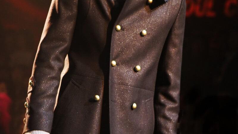 Körper eines männlichen Models in Mantel auf dem Laufsteg