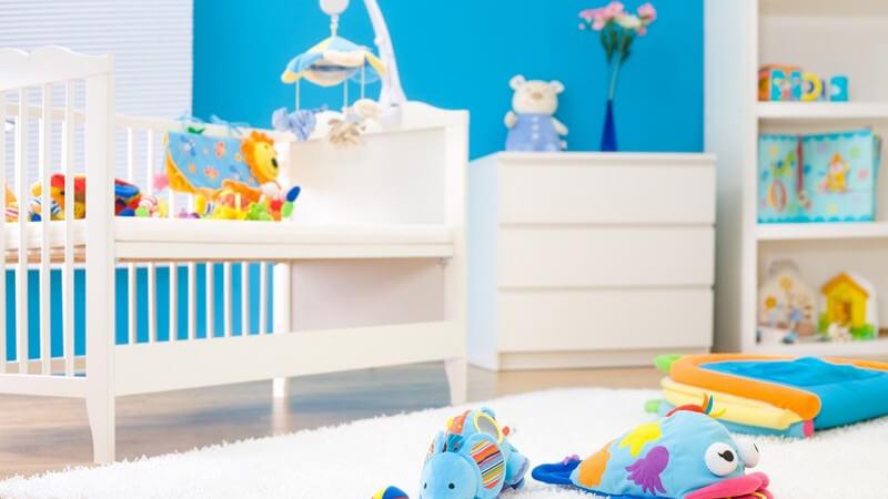 Ausschnitt Kinderzimmer mit blauer Wand, weißen Möbeln, buntem Spielzeug
